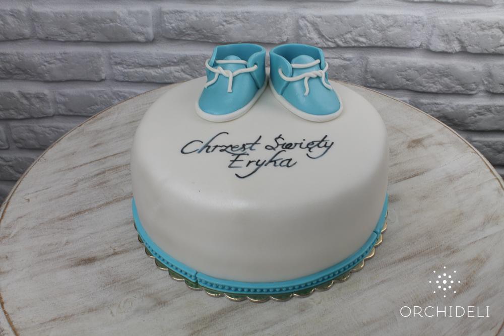 biały tort na chrzciny z niebieskimi bucikami z lukru plastycznego