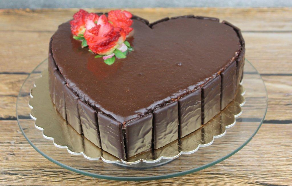 Tort red velevet w kształcie serca, polany czekoladą, orchideli tort w kształcie serca polany czekoladą mleczną z dekoracją ze świeżych truskawek