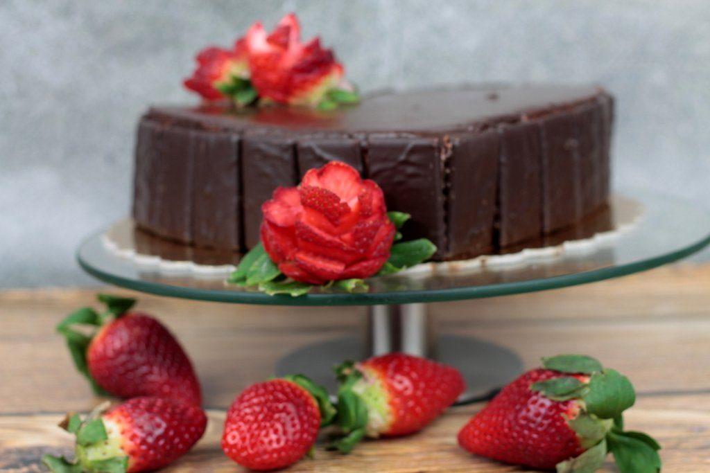 Orchideli-tort czekoladowy w kształcie serca, polany polewą czekoladową i dekorowany świeżymi truskawkami