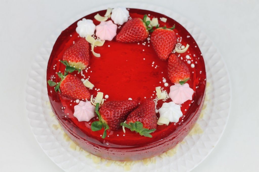 Tort urodzinowy z wiśniową galaretką i truskawkami, orchideli