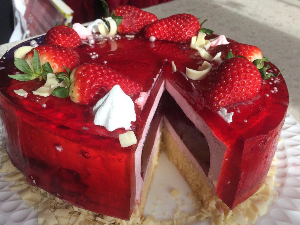 Tort urodzinowy z wiśniową galaretką i truskawkami, orchideli - urodzinowy tort malinowy oblany wiśniową galaretką, dekorowany świeżymi truskawkami i bezami, tort urodzinowy z wiśniową galaretką i truskawkami