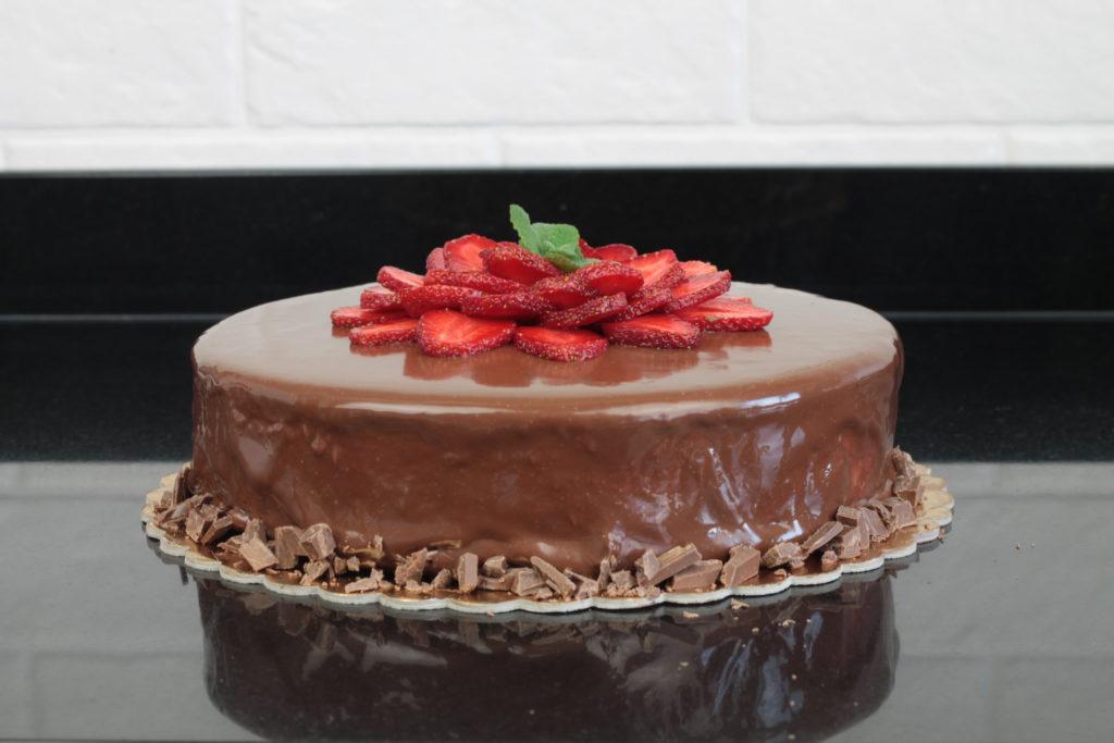 orchideli - tort czekoladowo-truskawkowy polany mleczną czekoladą z dekoracją z truskawek